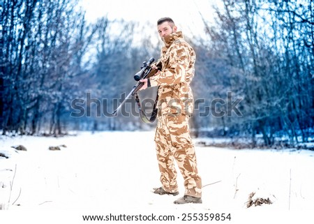 Army sniper during military operation using a professional rifle on a cold winter day - stock photo