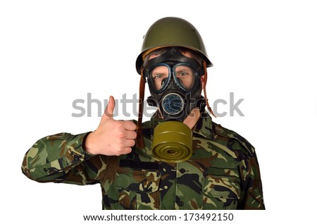 Army Soldier with Green Helmet And Gas Mask Giving thumbs up - stock photo