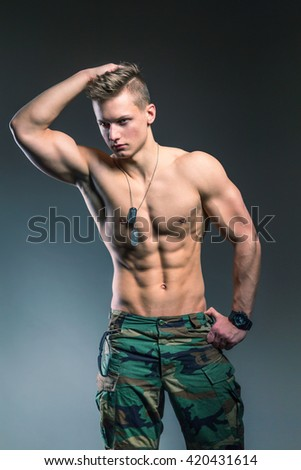 Army style shirtless man with muscular torso - studio image