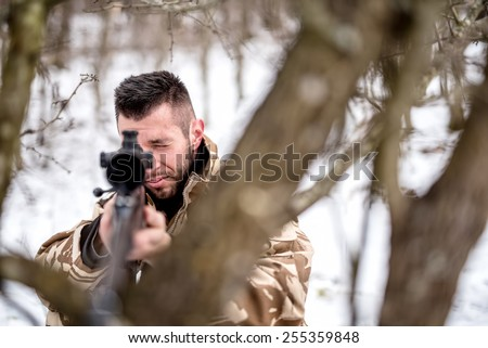 Army trooper with sniper on battlefield, using trees as camouflage  - stock photo