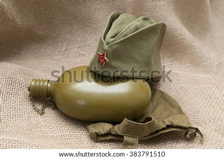 Army water bottle and cap with a star on the background fabric. - stock photo
