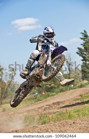 ARNCOTT, UK - JULY 22: An unnamed Moto-X rider leaps sideways off of the tabletop jump during a riders open practice session for the Expert class at Arncott MX Park on July 22, 2012 at Arncott. - stock photo