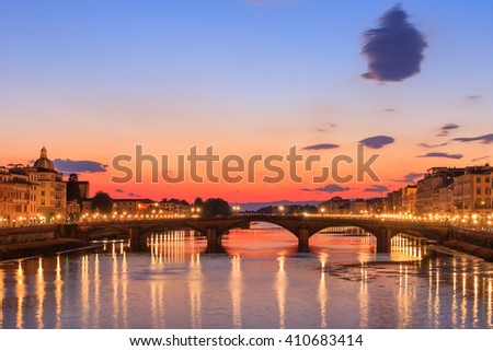 Arno River of Florence at dusk with red sky and reflections of city lights in the river