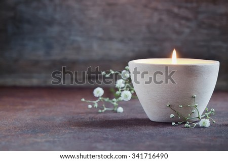 Aroma candle decorated with flowers, spa concept - stock photo