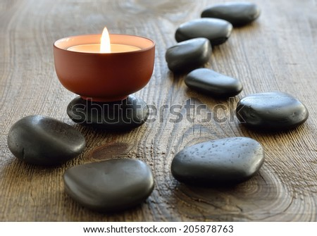 Aroma candle with spa stones on a wooden background. Selective focus