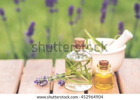 aroma essential spa oil and natural fragrance oil with lavender flower on wooden table over blurred lavender garden, image for aroma spa alternative therapy medicine and meditation concept. - stock photo