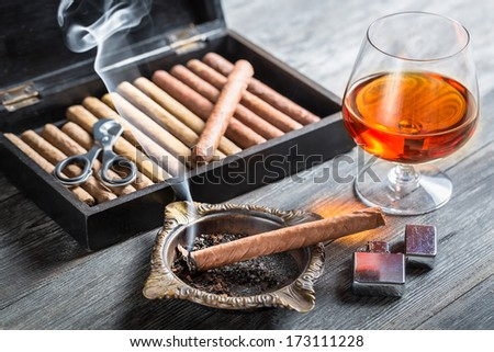 Aroma floating up from cigar and cognac in glass - stock photo