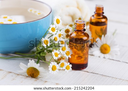 Aroma oil with chamomile on wooden background. Spa and wellness setting. Selective focus. - stock photo