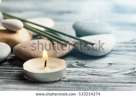 Aroma sticks, pebbles and lit candle in a SPA composition. Toned blue