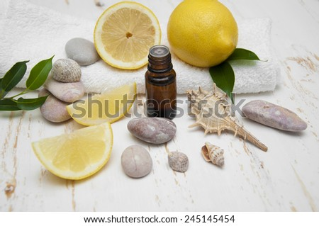 Aromatherapy accessories with lemon fruit halves over white background - stock photo