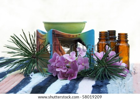 Aromatherapy Aroma Oil in Glass Bottles and Candle Bowl Decorated - stock photo