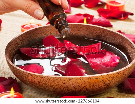 Aromatherapy. Essence oil. Spa treatment Beauty Spa treatment. Bowl of water with red rose petals - stock photo