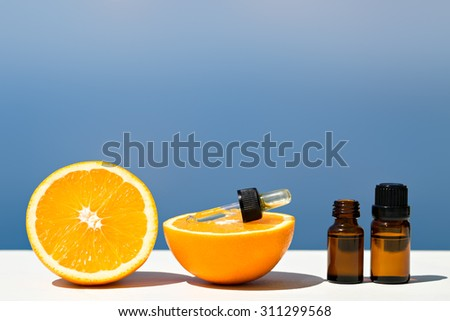 Aromatherapy essential oils in bottles with oranges - stock photo