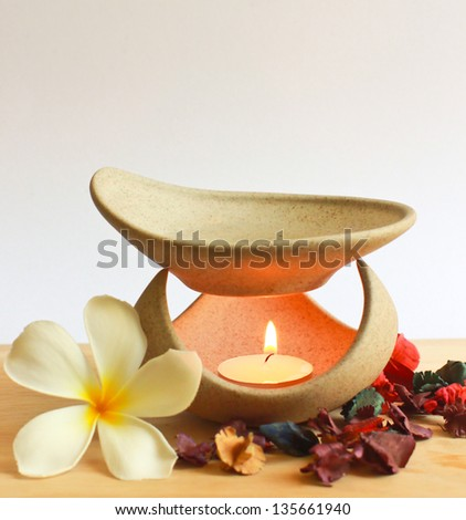 Aromatherapy lamp with flower and candle - stock photo