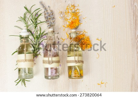 Aromatherapy massage oils. Row of essential oils in glass bottles, rosemary, lavender and calendula,  on the wooden board. - stock photo