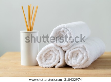Aromatherapy reed diffuser air freshener with stack of white towel - stock photo