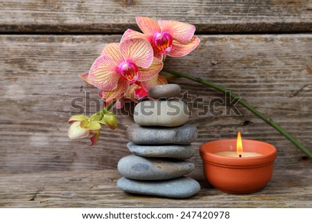 Aromatherapy spa set. Zen stones, candles and orchid on wooden background - stock photo