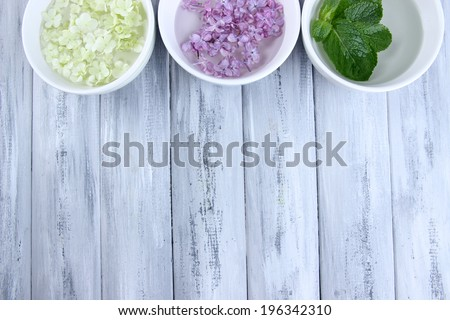 Aromatherapy treatment bowls with flowers and perfumed water on wooden background - stock photo