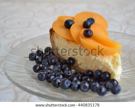 Aromatic cheesecake with apricot slices and blueberry on a glass plate. Healthy breakfast. Soft focus. - stock photo