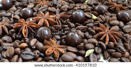 Aromatic coffee beans background with glitter chocolate balls and flavoring. - stock photo