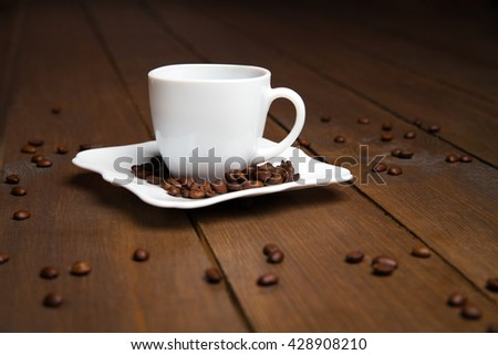 Aromatic coffee in white cup with saucer and scattered beans - stock photo