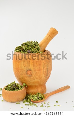 Aromatic dry Wild Thyme in wooden mortar, wooden bowl and wooden teaspoon over white background - stock photo