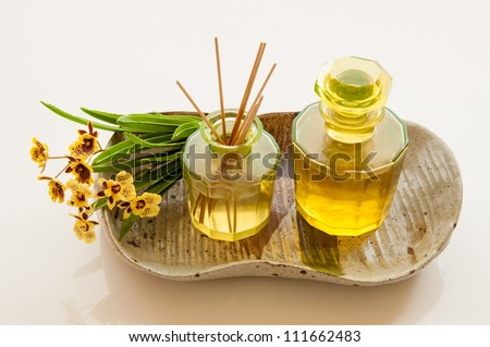 Aromatic essence oil bottle with bottle of fragrance reeds diffuser and bunch orchid flower.