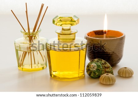 Aromatic essence oil bottle with bottle of fragrance reeds diffuser, candle and shells.