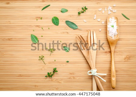 Aromatic herbs and spices  green mint ,fennel ,oregano, sage,lemon thyme and peppermint with fork and sea salt on  bamboo cutting board.
