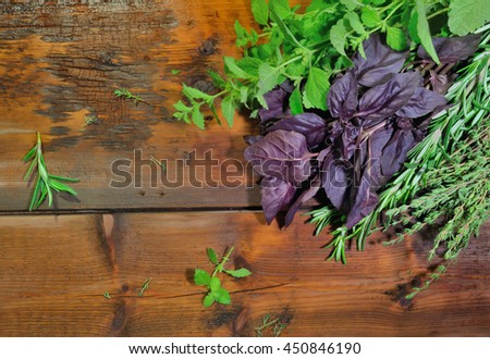 Aromatic herbs (rosemary, thyme, basil, mint)  on wooden background. Overhead view
