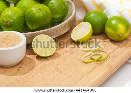 Aromatic limes on wooden chopping board; Cocktail lounge; Ingredients for cocktail or sweet-and-sour drinks; Fresh limes and cane sugar - stock photo