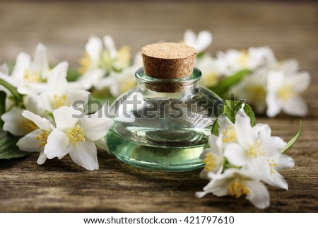 Aromatic oil with jasmine flower on rustic wooden table - stock photo