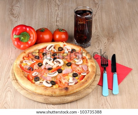 Aromatic pizza and cola on wooden background