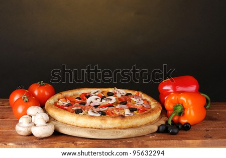Aromatic pizza with vegetables and mushrooms on wooden table on brown background - stock photo
