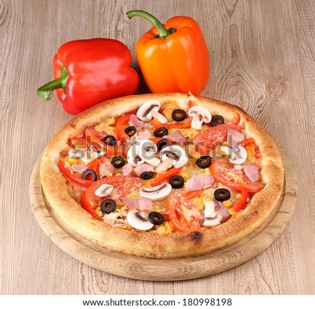 Aromatic pizza with vegetables on wooden background - stock photo
