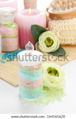 Aromatic salts in glass bottles and spa treatment, on bamboo mat,  isolated on white - stock photo