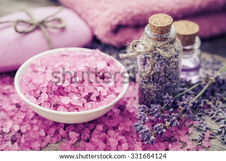 Aromatic sea salt, bottle of dry lavender, essential oil and lavender flowers. Bar of homemade soaps and towel on background.  Selective focus. - stock photo