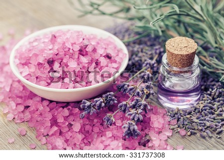 Aromatic sea salt, bottle of essential oil and lavender flowers. Selective focus. - stock photo