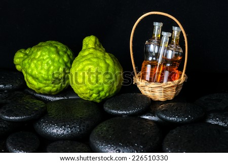 Aromatic spa concept of bottles essential oil in basket, bergamot and zen basalt stones with dew on black background - stock photo