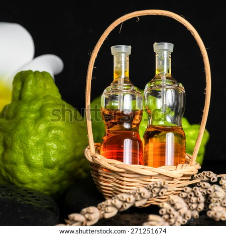 Aromatic spa concept of bottles essential oil in basket, flower, bergamot, candles and black zen basalt stones with dew