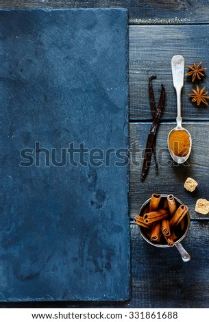 Aromatic spices, vanilla and cinnamon sticks over dark wooden and stone background with space for text. Christmas and holidays concept. Top view. - stock photo