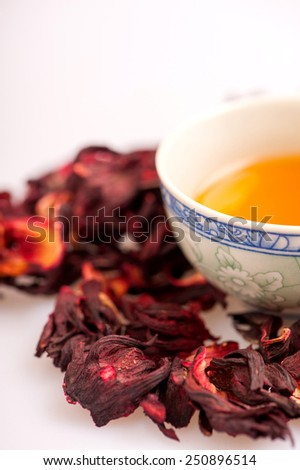 Aromatic tea. Image of a cup of tea surrounded by flower tea composition isolated on white background with selective focus - stock photo