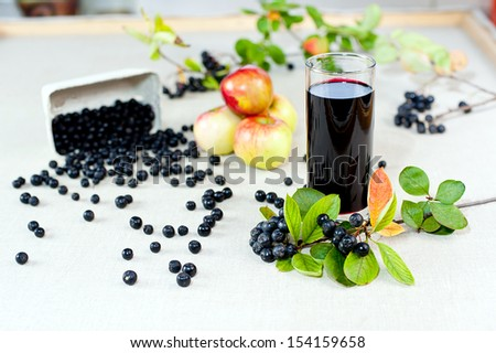 Aronia - Black Choke berry fruits and juice. Separated pile of fruit, twig with leaves, and bunch.