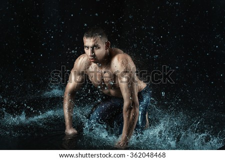 Around the man splashes water. Man with an athletic figure.