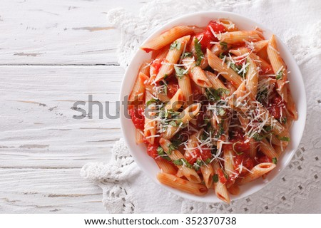 Arrabiata pasta penne with Parmesan cheese on a plate. horizontal top view