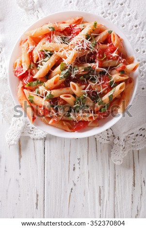 Arrabiata pasta penne with Parmesan cheese on a plate. vertical top view - stock photo