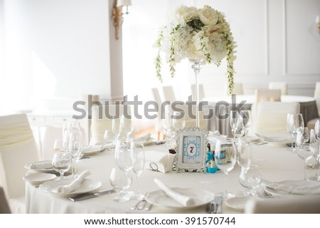 arranged festive white table with bouquet - stock photo