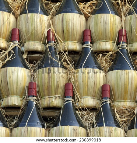 arranged many chianti wine bottles  ( traditionally in straw basket, called fiasco, plural fiaschi ),Florence, Tuscany, Europe - stock photo