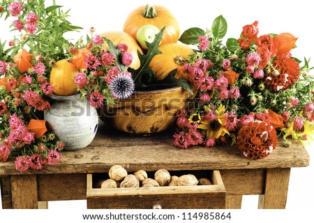 arranged still life of pumpkins and flowers