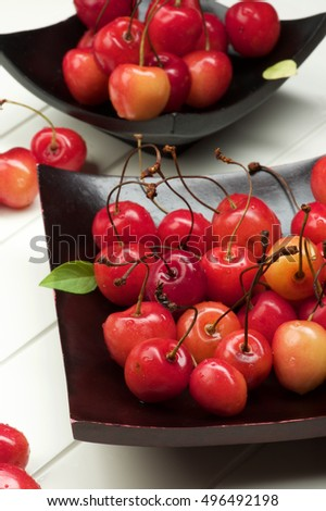 Arrangement Fresh Ripe Sweet Maraschino Cherries on Black Wooden Plates Cross Section on Plank White background. Focus on Foreground